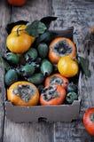 En la tabla en una caja mandarines de un caqui fresco, del feijoa y de la fruta cítrica Fotografía de archivo
