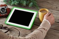 En la tableta blanca del primer de madera de la tabla, la taza de café, la cámara del vintage y una puntilla de la picea Foto de archivo