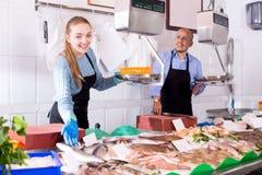 En la tienda que ofrece al ayudante de los jóvenes de los pescados frescos Imágenes de archivo libres de regalías