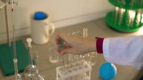 En laboratorio el bioquímico de sexo femenino sacude los tubos de ensayo con las muestras líquidas almacen de metraje de vídeo