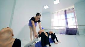 En lagledare undervisar balettflickor sträckning stock video