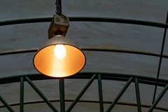 En lampa med orange ljus hänger på taket av ett växthus royaltyfria foton