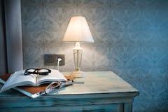 En lampa och en bok på en nattduksbord i ett hotellrum Royaltyfria Bilder