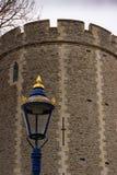 En lampa står ut i guld- och blåttglans mot den tråkiga stenhuggeriarbetet av medeltida befästningar fotografering för bildbyråer