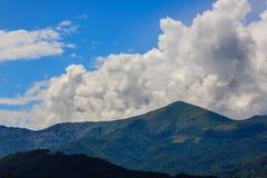 En landskap symmetri av berg och moln Arkivfoto