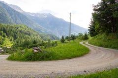 En landsväg i de schweiziska alpsna Arkivbild