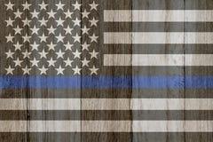 En lantlig gammal tunn blålinjenflagga på ridit ut trä Arkivbild