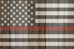 En lantlig gammal tunn röd linjeflagga på ridit ut trä Royaltyfria Bilder