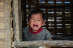 En Laotian behandla som ett barn gråt på fönstret av hans traditionella hem arkivfoto