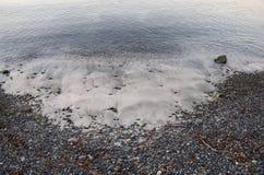 En lapp av sand på en grusstrand Royaltyfria Foton
