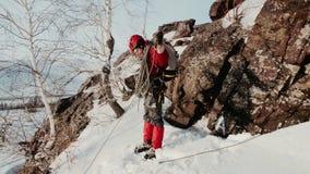 En las cuestas de la montaña es un escalador en una chaqueta roja y los vidrios, caen un enredo de cuerdas que suben después metrajes