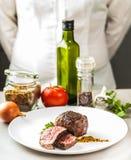 En las especias de la tabla, las verduras y un plato del medallón frito Foto de archivo libre de regalías