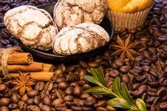 En las habas dispersadas del café hay una placa con las galletas del chocolate al lado de los palillos de la torta del canela y d Foto de archivo