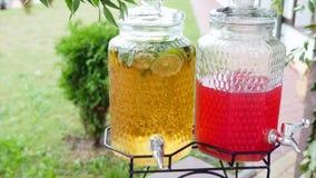 En las latas del tablero dos de soda Bebidas - limón y cal Luz difundida Rebanadas de fruta cítrica en un tarro en la tabla metrajes