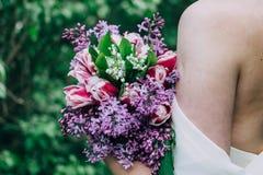 En las manos de la muchacha un ramo de lilas fotografía de archivo