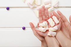 En las manos del caramelo dulce del aire de la mamá y del bebé Foto de archivo libre de regalías