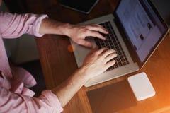 En las manos del hombre del tiro que trabajan en el ordenador imagen de archivo libre de regalías