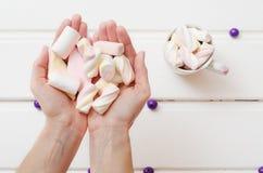 En las manos delicadas de muchachas, aire, caramelo dulce Fotografía de archivo libre de regalías