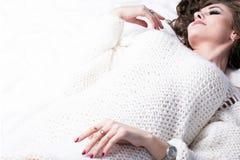 En las mentiras de la cama del blanco una muchacha hermosa en un suéter hecho punto Lugar para el copyspase Imagenes de archivo
