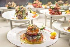 En las placas presentadas muchas verduras y carne, todos se rellenan con la carne picadita, pimienta, tomates, tocino imagen de archivo