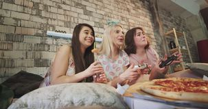 En las señoras modernas de un dormitorio que disfrutan del tiempo así como la pizza y un poco de botella de bebidas que juegan en almacen de metraje de vídeo