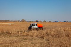 En lastbil för trans. av bensin och bränsle med en orange behållare rider i ett gult fält på vägen under leveransen av royaltyfri foto