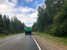 En lastbil, en traktor med en stor grön släp kör längs en skogasfaltväg med gröna träd på jordningen fotografering för bildbyråer