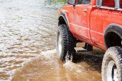 En lastbil 4wd på den översvämmade vägen Arkivfoton