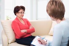En äldre kvinna som talar till psykologen Arkivfoton