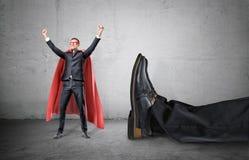 En le affärsman i en röd udde för superhero med händer som lyfts i framgångrörelseanseende bredvid en jätte- mänsklig fot Arkivbild