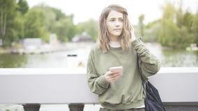 En le brunettflicka lyssnar till en musik som dricker utomhus en kopp kaffe Royaltyfria Foton