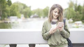 En le brunettflicka lyssnar till en musik som dricker utomhus en kopp kaffe Royaltyfri Fotografi