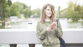 En le brunettflicka lyssnar till en musik som dricker utomhus en kopp kaffe Royaltyfri Foto