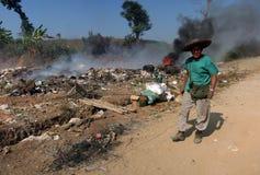 En le Burmese man som framme står av en hög av brinnande avfall arkivfoton