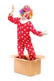 En le clown som kommer ut ur en kartong Arkivbild