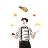 En le farskonstnär som jonglerar frukter Arkivbild