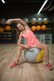 En le flicka som gör konditionövningar Sportkvinna som sträcker på en passformboll på en idrottshallbakgrund Öva begrepp Fotografering för Bildbyråer