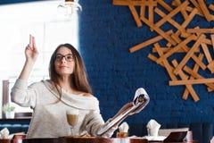 En le kvinna i en restaurang med menyn i händer Arkivbild