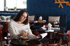 En le kvinna i en restaurang med menyn i händer Royaltyfri Fotografi