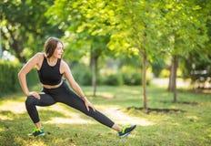 En le kvinna med charmigt långt ljust hår gör sträckning i den stora gräsplanen parkerar Den sportiga damen Arkivfoto
