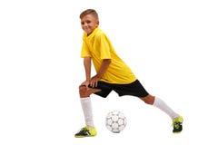 En le liten fotbollsspelaresträckning Ett gladlynt barn i en fotbolllikformig som isoleras på en vit bakgrund sportar Arkivbild