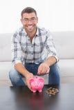 En le man som sätter mynt i en spargris Arkivfoto