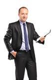 En le ung affärsman som rymmer en clipboard royaltyfri bild