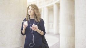 En le vit flicka för brunett lyssnar till musik utomhus Arkivfoto