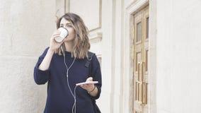 En le vit flicka för brunett lyssnar till musik utomhus Royaltyfria Foton