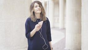 En le vit flicka för brunett lyssnar till musik utomhus Royaltyfri Fotografi