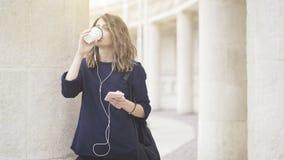 En le vit flicka för brunett lyssnar till musik utomhus Royaltyfri Bild