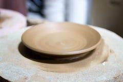 En ledar- ceramist med 13 år av erfarenhet gjorde flera plattor från röd lera på keramikers hjul, på ett ark av royaltyfri bild