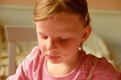En ledsen gullig liten flicka En liten flicka ser SAD ner En liten flicka sitter i köket Fotografering för Bildbyråer