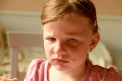 En ledsen gullig liten flicka En liten flicka ser SAD En liten flicka sitter i köket Royaltyfri Fotografi